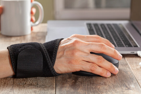 Chronic trauma to the wrist joint  in people using computer mouse may lead to disorders that cause inflammation and pain. A woman working on desk uses wrist support brace and ergonomic vertical mouse