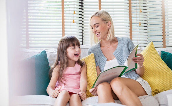 Portrait of beautiful caucasian mother hold story book reading teaching daughter little girl. Teacher home school bedtime story learning, education happy family love together mother's day holiday.