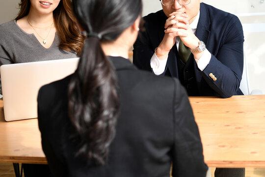 おしゃれなオフィスで複数の男女の面接官による面接採用試験のイメージ