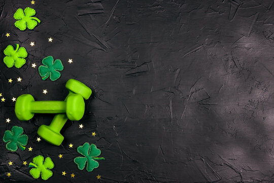 Green dumbbell with decorative clover leaves and gold stars on black background.