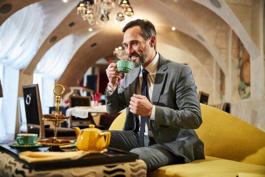 Inspired gentleman enjoying his tea at a hotel lobby