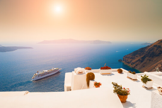 Beautiful sunset at Santorini island, Greece. White architecture on the rocks with sea view. Famous travel destination