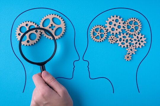 Human brain is made gear mechanism on blue background. The brain is viewed through a magnifying glass. Two different thought processes.