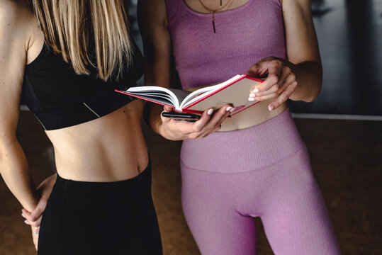 two slender girls in sportswear doing yoga exercises and reading a book