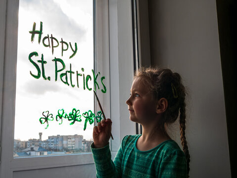 Drawing St. Patrick's Day Child painting green three-leaved shamrocks indoor, festive home decoration, quarantine family leisure. Little girl draws clover on window glass. Stay home concept New normal