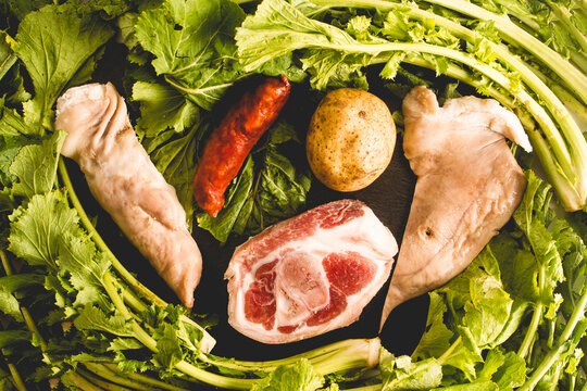 overhead view ingredients of the Galician stew recipe during carnivals consisting of potato, pork leg, lacon, smoked ear, chorizo ​​and turnip greens
