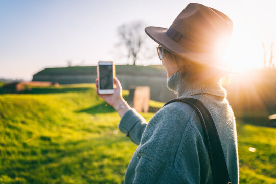 Beautiful cheerful adult woman in felt hat and sweater making selfie on smartphone on a sunny spring day