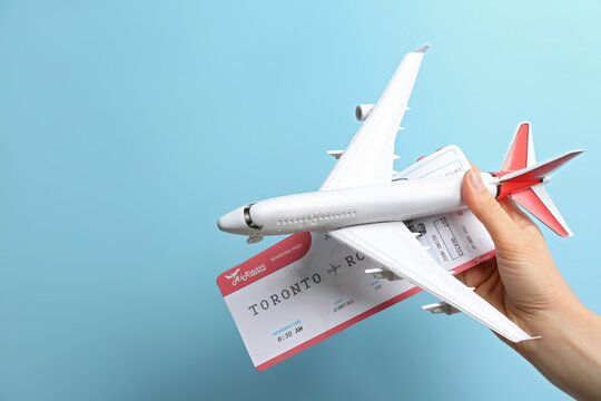 Woman holding toy airplane and tickets on light blue background, closeup
