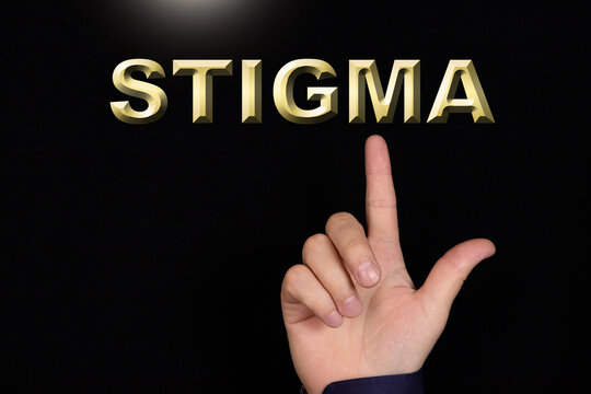 STIGMA text, a word written on a black background pointed to by a hand with the index finger of a person.