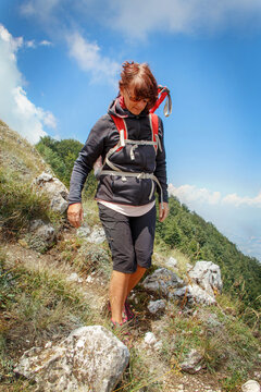 Middle age woman hiking in mountains in a sunny day