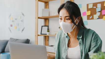 Asia businesswoman wearing medical face mask using laptop talk to colleagues about plan in video...