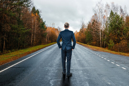A businessman in a business suit stands on the road, a long way in front. Development concept, start-up, investment search.