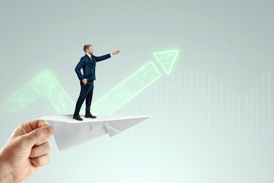 Startup. Businessman flying on a paper airplane with the pushing hand of an investor. Concept for opportunities, investments, business trends, business angels.
