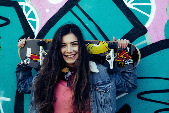 Girl with skateboard graffiti wall background