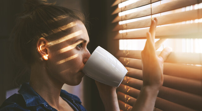 woman looking through window blinds into the sunlight and drinking coffee