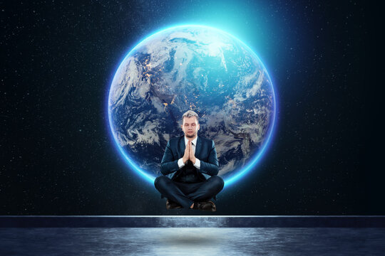 A businessman levitates in a lotus position against the background of the globe. Mixed media. Concept Global networks and international business. Elements of this image furnished by NASA