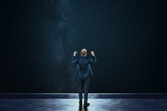 Rear view businessman stands against the background of the starry sky. Mixed media. Concept Dream, success, opportunity, development.