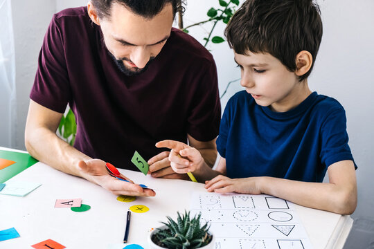 Autism awareness concept. Autism schoolboy during therapy at home with his tutor with learning and having fun together.