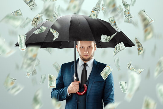 A man in a business suit with an umbrella stands against the background of falling dollars, rain of money. Business concept, bookmaker, sports betting, investment, passive income.