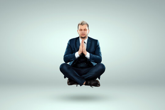 Creative background, Businessman in a business suit levitates in the lotus position on a light background. The concept of nirvana, calmness, relaxation, smoke break.