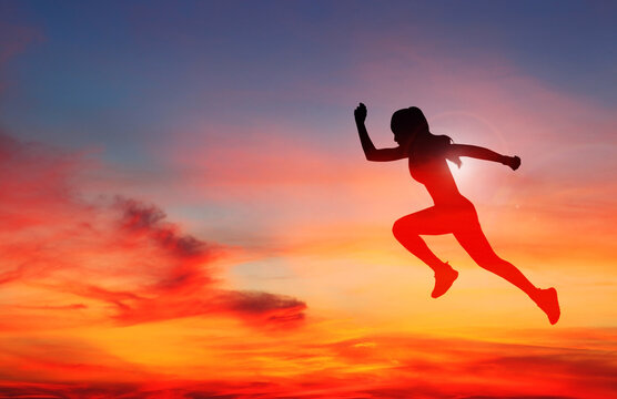 Woman runner in silhouette on colour sky background. Dynamic movement. Side view