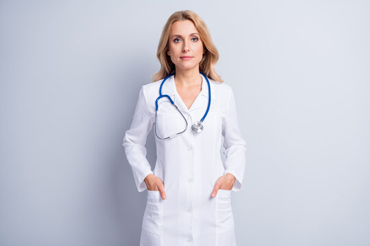 Photo of charming person put hands in pockets stethoscope hang on neck isolated on grey color background