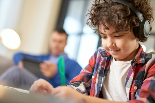 Close up portrait of latin american school boy wearing headphones, preparing homework while sitting at the desk at home