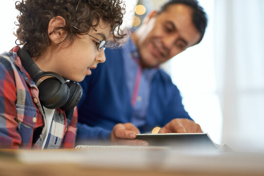Enthusiastic latin boy wearing glasses looking focused while sitting at the desk together with his father and doing homework during remote learning at home