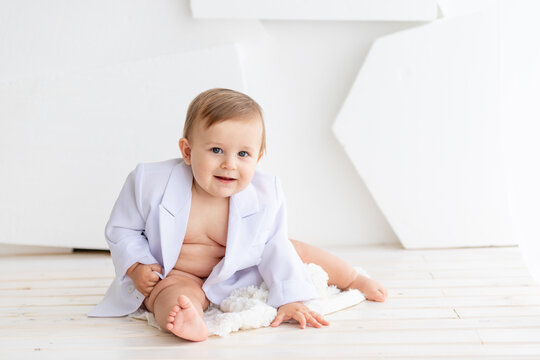 a small fat baby six months old in a white jacket and diapers sits on a light background, space for text