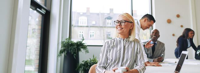 Fototapeta Smiling young businesswoman enjoying her coffee during an office break obraz
