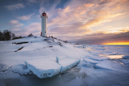 Graceful white lighthouse staying on the rocky coast covered with snow and ice at sunset. Russia, Leningrad oblast, Gulf of Vyborg