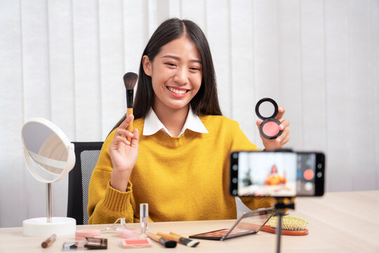 Asian woman present beauty cosmetic product and broadcast live video to social network by internet at home, beauty blogger concept.