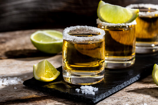 shots of gold Mexican tequila with lime and salt. Alcoholic Mexican national drink