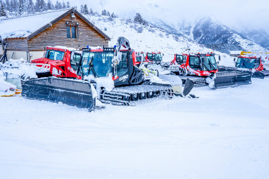 AURON, FRANCE - 02.01.2021: Snow plow trucks under the snow on a parking in the ski resort mountains. . High quality photo