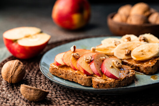 Toasts with peanut butter, apple, banana, walnut and honey. Healthy vegetarian breakfast concept.