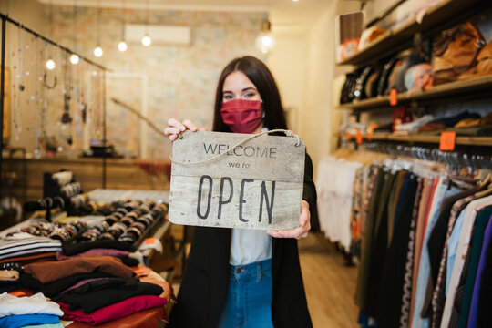 """Portrait of a beautiful young clothing store sales assistant holding the """"Welcome we're open"""" sign at the business entrance wearing a face mask during the Coronavirus Covid-19 pandemic"""