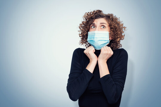 Young pretty girl in a black turtleneck with a respiratory mask on her face is afraid of infection on blue background