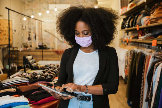 Portrait owner of clothing store at entrance of new business with tablet in hand analyze sales, new orders to be sent and check stocks wearing protective face mask during Coronavirus Covid-19 pandemic