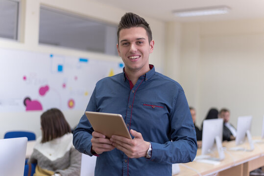 Portrait of casual turkish male student holding tablet or ipad inside modern computerlab classroom. Technology and education concept