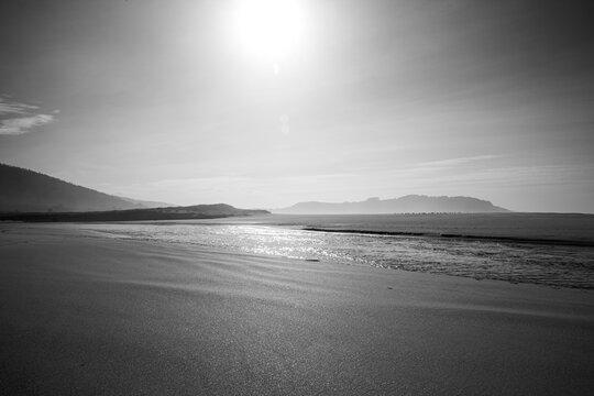 Preciosa playa de Esmelle iluminada por la luz del atardecer con un río cruzándola y con las montañas de fondo.