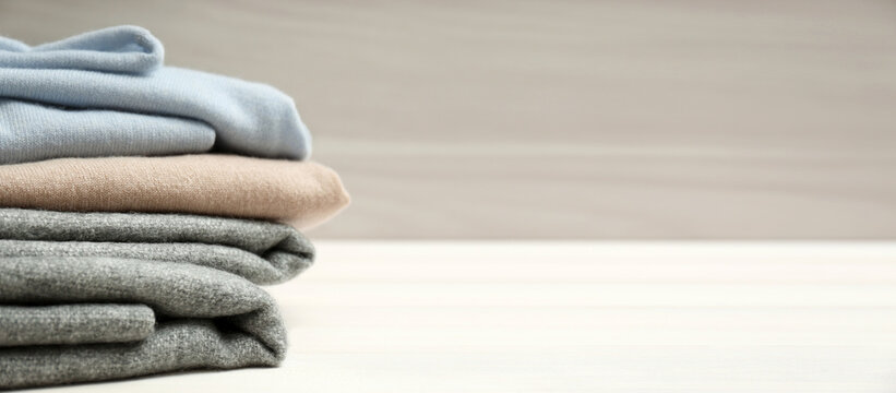 Stack of cashmere clothes on wooden table, space for text. Banner design