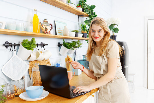 Young pretty girl stands in the home kitchen with laptop on the table
