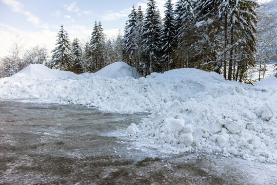 Big piles of snow from plowing on a road.