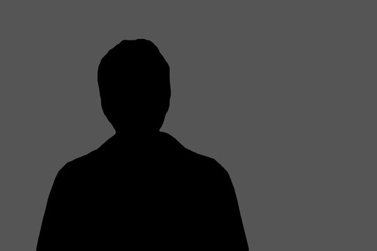 the black silhouette of an unknown person on a gray background copies the space. the concept of an anonymous person