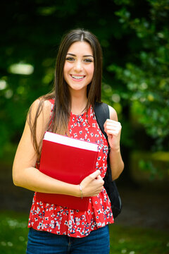 Beautiful female student holding a book outdoor
