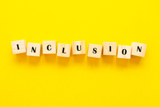 Inclusion concept word on wooden cubes on yellow background