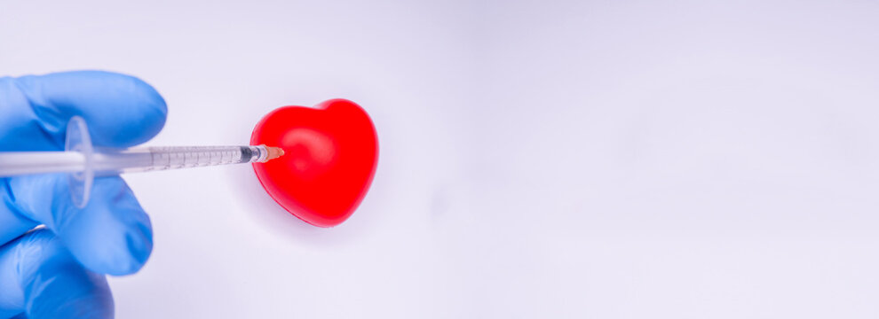 a hand in a medical glove holds an ampoule containing the covid-19 vaccine, invented to prevent the spread of the virus around the world. mask with a red heart on a white background Copy Space