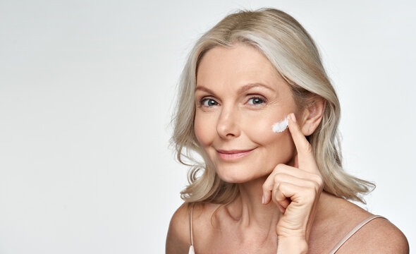 Smiling 50s middle aged mature older woman applying facial cream on face looking at camera isolated on white background. Anti age healthy dry skin care beauty therapy concept, old skincare treatment