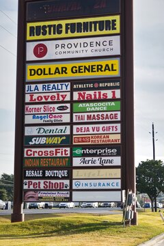 Humble, Texas USA 11-20-2019: Vertical signpost advertising many local businesses in a strip mall in Houston, TX.
