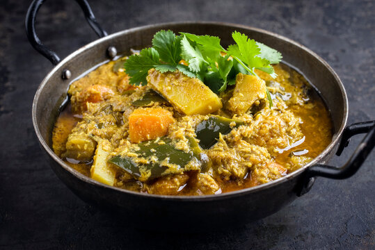 Traditional Indian sweet potato curry with eggplant served as top view in a design bowl